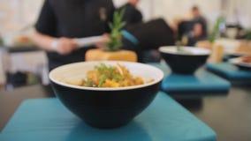 Arroz cozinhado em uma placa em uma tabela, fim acima Câmera zumbindo Arroz amarelo tradicional com as ervas e os vegetais, saudá video estoque