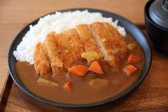 Arroz de curry con la comida japonesa frita del tonkatsu del cerdo en la tabla de madera imagenes de archivo