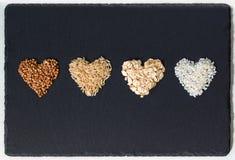 Arroz del alforfón, del arroz moreno, de la harina de avena y de la leche en formas de corazones fotografía de archivo libre de regalías