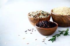 Arroz del arroz blanco del jazmín, del marrón, negro y rojo Surtido mezclado de granos en cuencos de madera en fondo concreto gri Fotografía de archivo libre de regalías