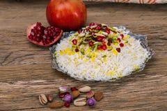 Arroz e tahchin persa do Oriente Médio tradicional do açafrão, porcas e romã em um fundo de madeira Foto de Stock Royalty Free