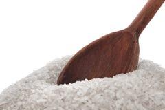 Arroz e uma colher de madeira Fotografia de Stock Royalty Free