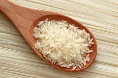 Arroz em uma colher de madeira no fundo dos macarronetes de arroz Foto de Stock