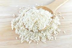 Arroz en cuchara de madera en el arroz y fondo de madera Imagen de archivo libre de regalías