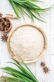 Arroz en placa y anís de madera en el fondo de madera blanco Arroz y especias en envase ecológico fije para cocinar Fije para el  Imagen de archivo libre de regalías