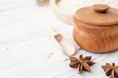 Arroz en placa y anís de madera en el fondo de madera blanco Arroz y especias en envase ecológico fije para cocinar Fije para el  Fotografía de archivo libre de regalías