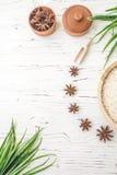 Arroz en placa y anís de madera en el fondo de madera blanco Arroz y especias en envase ecológico fije para cocinar Fije para el  Foto de archivo libre de regalías
