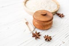 Arroz en placa y anís de madera en el fondo de madera blanco Arroz y especias en envase ecológico fije para cocinar Fije para el  Fotografía de archivo
