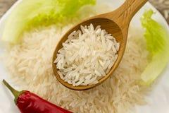 Arroz en una cuchara de madera en una placa del fondo, ensalada verde, pimienta del grano de chile Consumición sana, dieta, veget Fotos de archivo