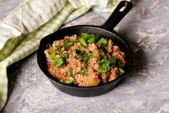 Arroz fritado com carne e salsa em uma frigideira do ferro fundido Foto de Stock