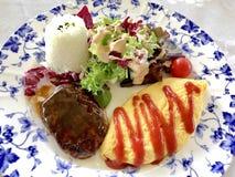 Arroz japonés de la hamburguesa y de la tortilla con la ensalada foto de archivo