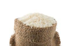 Arroz largo blanco en pequeño saco de la arpillera en el backgroun blanco Imagen de archivo