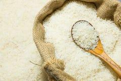Arroz lustrado do jasmim e colher de madeira no saco de gunny Fotos de Stock Royalty Free