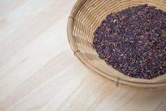 Arroz negro tailandés del jazmín y x28; Berry& x29 del arroz; en la cesta de bambú Fotos de archivo