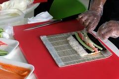 Arroz, pepino, carne de cangrejo, nori Las manos del ` s de los hombres en guantes transparentes, envuelven los ingredientes para Foto de archivo libre de regalías