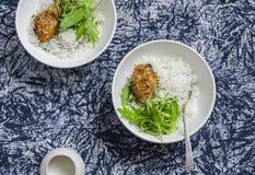 Arroz, pollo y ensalada en un cuenco en un fondo oscuro foto de archivo