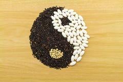Arroz preto e comprimido branco que formam um símbolo de yang do yin no wo marrom Fotografia de Stock