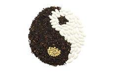 Arroz preto e comprimido branco que formam um símbolo de yang do yin no wo marrom Imagens de Stock Royalty Free