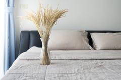 Arroz secado del árbol en una botella de cristal en la cama en el dormitorio Foto de archivo