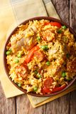 Arroz Valenciana with rabbit, chorizo, vegetables and spices in. A bowl on the table. vertical top view from above Stock Images