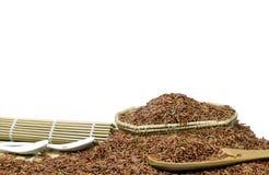 Arroz vermelho ou Riceberry e colher de madeira e cestaria Fotografia de Stock Royalty Free