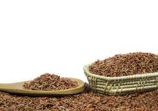 Arroz vermelho ou Riceberry e colher de madeira e cestaria Fotos de Stock Royalty Free