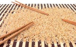 Arroz y palillos en la alfombra de bambú Fotos de archivo