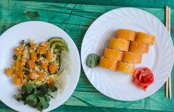 arroz y plato de color salmón del sushi con los pescados rojos en la placa blanca en vista lateral de madera verde de top del fon foto de archivo libre de regalías
