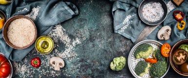 Arroz y verduras que cocinan los ingredientes, preparación en el fondo rústico, visión superior, bandera Alimento vegetariano san foto de archivo libre de regalías