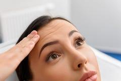 Arruga que muestra femenina sorprendida en cara Imagenes de archivo