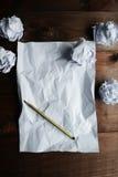 Arrugado encima de los papeles con una hoja del documento en blanco y de un lápiz sobre fondo de madera marrón Imagenes de archivo