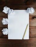Arrugado encima de los papeles con una hoja del documento en blanco y de un lápiz sobre fondo de madera marrón Fotografía de archivo libre de regalías