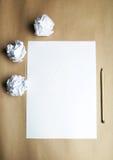Arrugado encima de los papeles con una hoja del documento en blanco y de un lápiz sobre fondo marrón Imagen de archivo