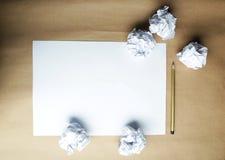 Arrugado encima de los papeles con una hoja del documento en blanco y de un lápiz sobre fondo marrón Foto de archivo