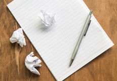 Arrugue el Libro Blanco y la pluma con el cuaderno en el escritorio de madera Imágenes de archivo libres de regalías