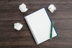 Arrugue el papel y la pluma con el cuaderno en el escritorio Imagen de archivo