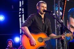 Arsen Mirzoyan bawić się gitarę i śpiewa podczas żywego koncerta przy otwarciem Roshen fontanna, Vinnytsia, Ukraina, 29 04 2017,  Zdjęcia Stock