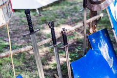 Arsenal of medieval knight swords and shield on wooden stand. Middle ages concept. Close up, selective focus Royalty Free Stock Image