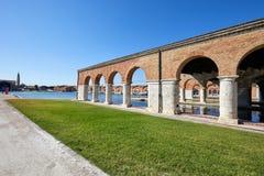 Arsenal veneciano con la arcada, el canal y la hierba verde en Italia imágenes de archivo libres de regalías