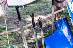 Arsenale delle spade e dello schermo medievali del cavaliere sul supporto di legno Immagine Stock Libera da Diritti