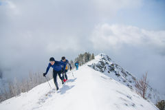 Arshan, Russia - 04.2015: A group of men skyrunning running with. Walking sticks in hands during a шт snow mountain marathon Royalty Free Stock Photography