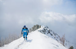 Arshan, Russia - 04.2015: young man skyrunning running with walk. Ing sticks in hands during a шт snow mountain marathon Royalty Free Stock Photography