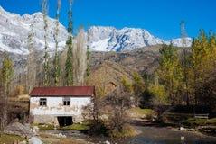 ARSLANBOB, QUIRGUIZISTÃO: Vista da vila de Arslanbob em Quirguizistão do sul, com as montanhas no fundo durante o outono fotografia de stock royalty free