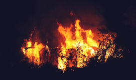 Arson or nature disaster - burning fire flame on wooden house roof. Big fire at night stock images