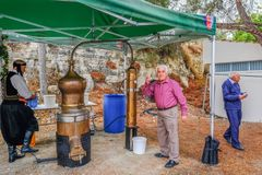 Distilling Zivania at a Cypriot festival. Arsos Village, Cyprus - October 8, 2017: Man toasting with Zivania from a working still at a village festival Royalty Free Stock Images