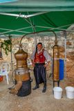 Traditionally dressed man posing with his working still. Arsos Village, Cyprus - October 8, 2017: Man in traditional Cyprian dress posing with his still for Royalty Free Stock Photo