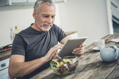 Artículo afirmado de la lectura del hombre sobre la tableta fotografía de archivo libre de regalías