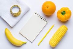 Artículos amarillos Concepto de la aptitud con el plátano, moneda, naranja, cinta métrica en el fondo blanco Visión desde arriba Fotografía de archivo libre de regalías