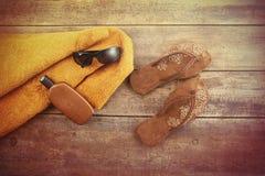 Artículos anaranjados de la toalla y de la playa en la madera Imagenes de archivo