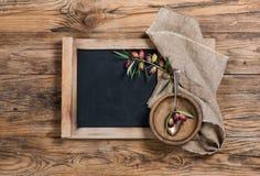 Artículos de cocina con la pequeña ramita en blanco de la pizarra y de la aceituna Fotografía de archivo libre de regalías